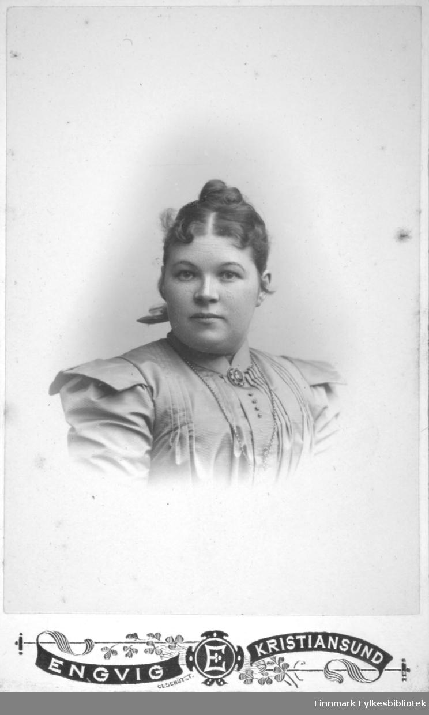 Portrett av fru Monsaas, fornavnet kan være Marie, på Ingøy i Måsøy kommune. Hun har en ganske lys bluse med skulderputer. En brosje ses på halskragen hennes og et tynt kjede henger rundt halsen og nedover brystet.