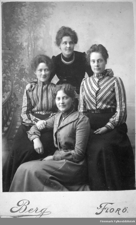 Gruppeportrett av fire kvinner. De har skjørt og kjoler i varierende form og farge. De to i midten har stripete bluser. Halskjeder ses rundt halsen på de to fremst og bakerst på bildet. Tapetet på veggen bak dem har naturmønster.
