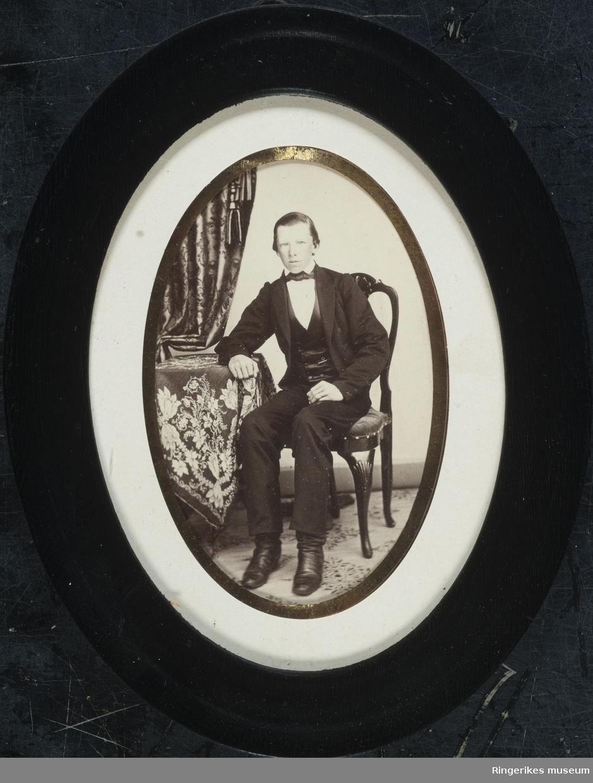 Svart oval ramme som viser et bilde av Erik Bjøre, pent antrukket, sittende ved et bord.