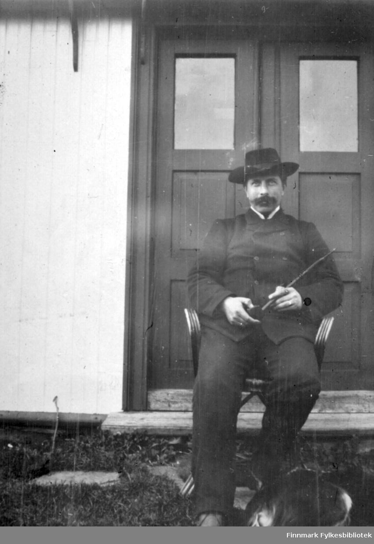 En mann sitter ute, rett foran et hus. Han har mørk dress med hvit skjorte og slips. Han en bredbremmet, mørk hatt på hodet. Han holder en pipe med langt stilk i hendene. Dobbel-døra bak han har tre speil med glass i to av dem. Husveggen har stående hvitt panel og en enkelt planke står på veggen rett utenfor døra