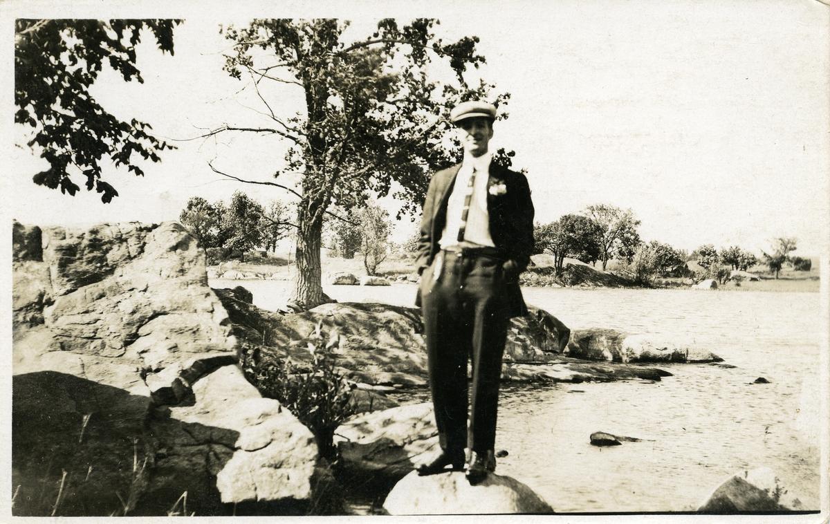 Mann med dress står på en stein i vannet. Prospektkort.