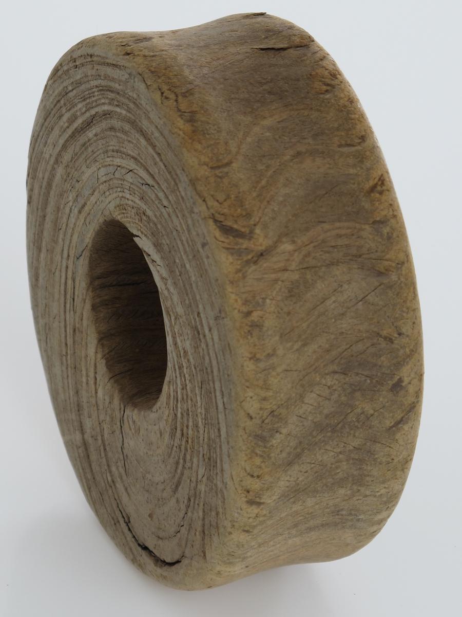 """Blokkskive av pukkenholt. Rund skive med hull midt i, rest av skylping på yttersiden. Dreid, boret hull til aksling, en blokknagle.  Til tau med anslagsvis 1 1/4 tomme tykkelse.    Tilstand: Noe slitasje etter å ha vært """"malt"""" mellom rullestein og sand i brenningene på Spornes."""