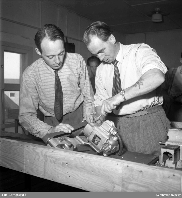 Omskolningsarbete på Verkstadsskolan. Män i skjorta och slips mekar med maskiner.