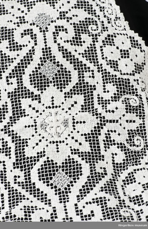 Stor rblomst i midten flankert av krukkelignende figurer, C-formet bord langs kanten med ispedde madaljonger i en sirkel rundt det hele.