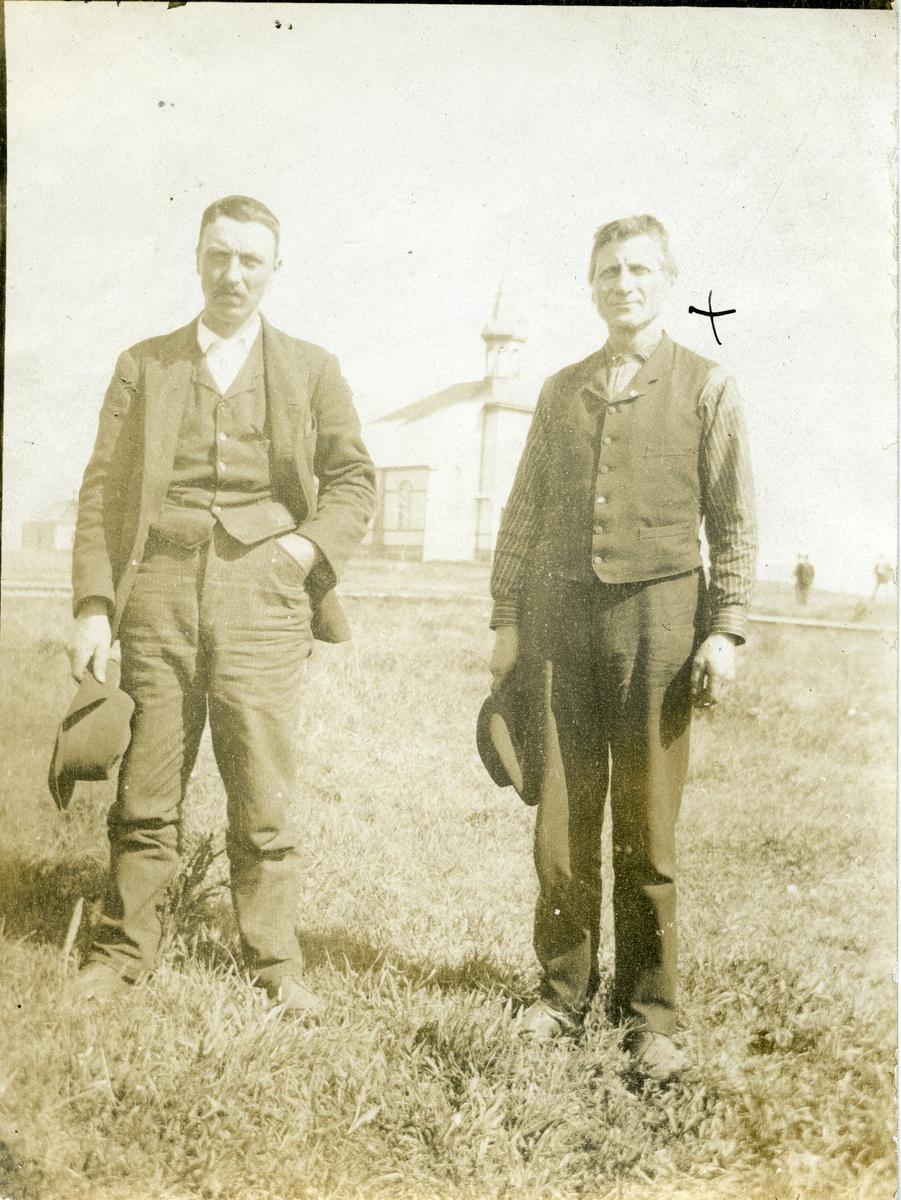 To menn avbildet foran en kirke. Mennene er iført hverdagsklær.