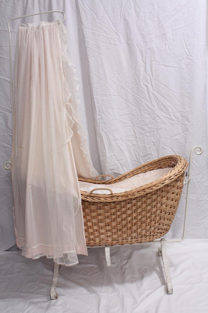 Voggen har et understell i metall med en opphengstang for drapering over hodeenden på korgen. Understellet er festet i hver ende på korgen slik at denne kan vogge sidelengs. Korgen er laget av flettede lyse trerøtter, med to håndtak på langsidene.  Innsiden på korgen er dekket av et vattert lyserosa teppe som kan knyttes fast. Det følger med et sett sengetøy; dyne og putevar som er dekorert med broderi og heklet bord. I bunnen ligger en skum-madras med et hvit laken.