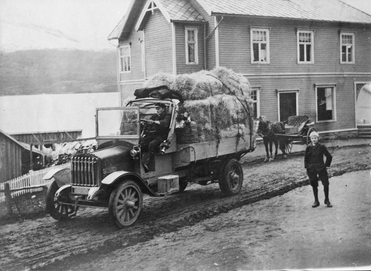 Lastebil foran Sjøveien Apotek. Bak bilen står en hestedrosje.