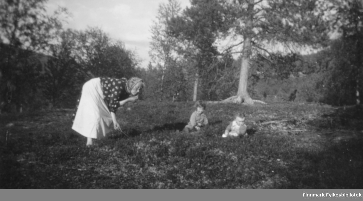 Karen Kristine Thomassen også kalt 'Moster' på tur i skogen med Karen Kristine Johansen g. Jakobsen to år, og Ragnhild Marie Johansen g. Suhr ett halvt år. 'Moster' var tante og søster til moren til Karen Thomine Lovise Johansen f. Kristensen, som er mor til barna. På bildet står 'Moster' bøyd og lukter på noe hun holder i hånden. Hun er kledt i et hvitt skjørt, og mønstret overdel. På hodet har hun et skaut. Barna sitter i lyngen. Det er trær rundt i området