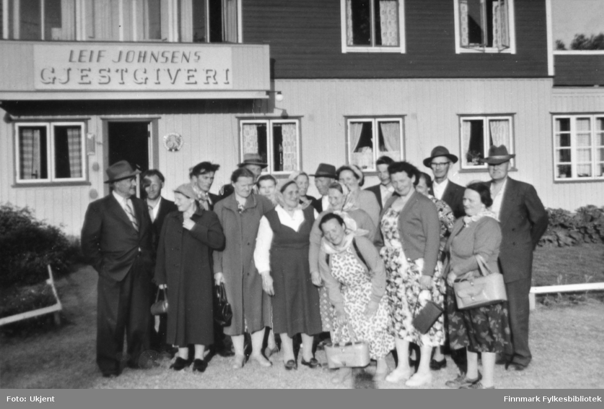 Nesseby husmorslag er ute å reiser. Her poserer de foran Leif Johnsens Gjestgiveri, Rustefjelbma, Tana. Kvinnene har på seg kjoler, skjørt, skjorter, strømpebukser og sko. Enkelte har på seg skaut, andre har briller. Kvinnene holder på vesker. På veggen kan man se vinduer med gardiner i.Blant kvinnen kan man se enkelte menn. Mennene har på seg hatter, jakker, slips og bukser.