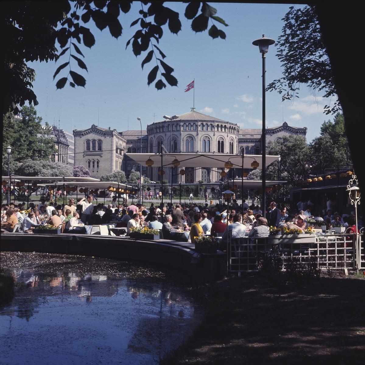 """Sommerdag i Oslo 1970. På uterestauranten Saras telt sitter det mange mennesker. I forgrunnen ses speilbassenget """"Spikersuppa"""". Bak er Stortinget."""