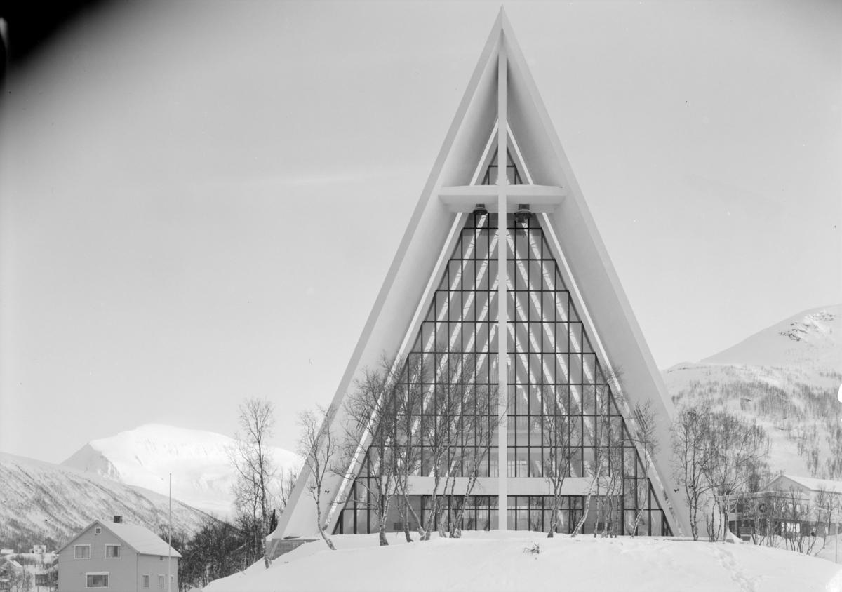 Arkitekturfoto av Tromsdalen kirke, bedre kjent som Ishavskatedralen. Med sitt avtrappede båthusformede eksteriør og sine åpne glassgavler er den blitt et landemerke i området. Kirken ble innviet 19. november 1965.
