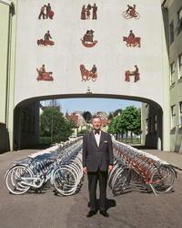 Fotografi av Jonas Øglend foran to rekker sykler fra fabrikk