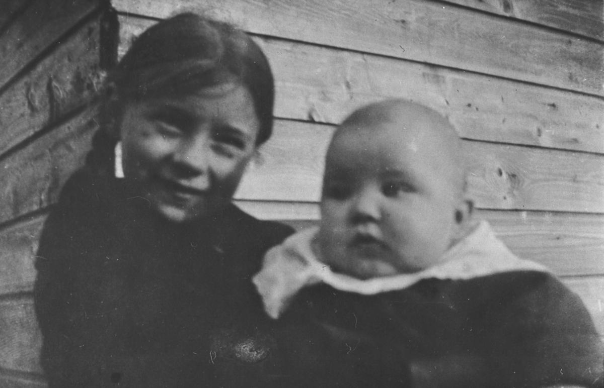 Bilde av Lilly Lein med lillebror Rolf. Hun i mørke klær og fletter, Han med stor hvit krave.Vi ser litt av en bygning bak.
