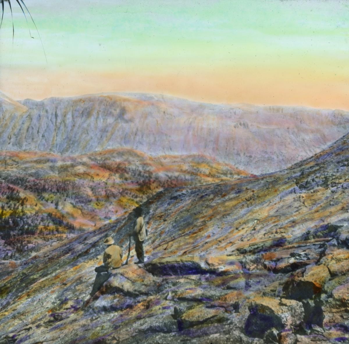 Håndkolorert dias. To menn skuer utover et nakent fjellandskap. En sitter på en store stein, den andre lener seg på en stav.