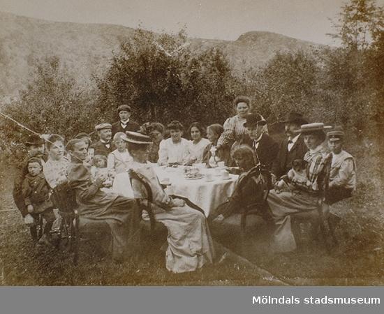 Män, kvinnor och barn sitter kring ett bord utomhus. Okända namn, plats och årtal.