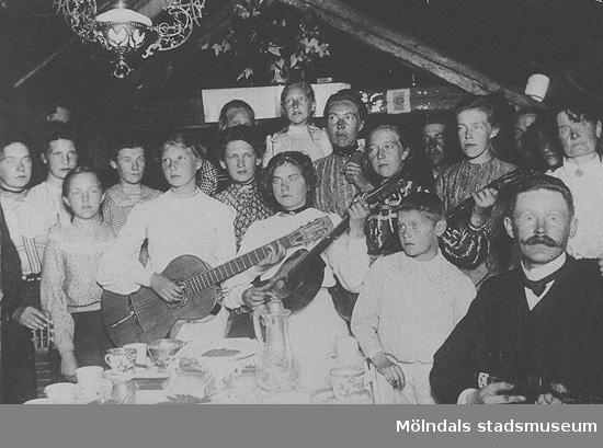Män, kvinnor och barn står vid ett kaffebord, några av dem håller i instrument. Okända namn, plats och årtal.