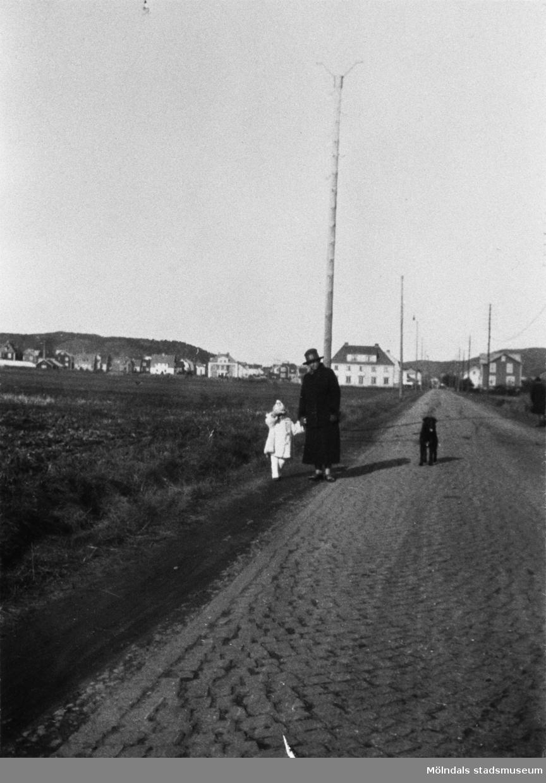 Kvinna och barn promenerar längs vägen.