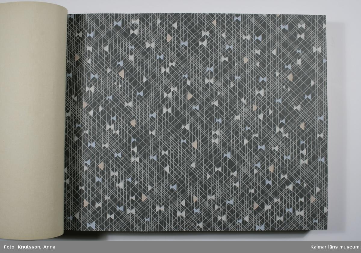KLM 28100:3. Tapet, tapetkatalog. Blå pärm i kartongpapper utan tryck på framsidan. Katalogen innehåller tapetprover i olika färger och utförande. Datering: 1950-tal.