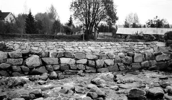 Forbygningsarbeider ved ei bru over Bronkåa, ei tilløpselv til Glomma fra vest i grensetraktene mellom Elverum og Våler kommuner.  Det kan synes som om elveløpet er rensket for stein, som er lagt opp i en mur på oversida av ei bru.  Også vegskråningen ved siden av er plastret med steinheller, antakelig med sikte på å forebygge utvasking av veggrunnen dersom elva under flom skulle gå over den nevnte muren med strømretning på tvers av vegbanen.  ifølge innskrift på fotografiet skal det ha vært vegvesenet som fikk lagt opp disse murene, som nok betydde mer som flomvern for veganlegget enn som ledeskjermer for fløtingstømmer.  Brua var ei enkel bjelkebru med rekkverk, til høyre for dette fotografiet.  På nedsida av vegen ser vi bølgeblikktekkete takene på noen av bygningene i et lite gardstun.  Bronkåa er cirka 20 kilometer lang, og den renner gjennom skog, så elva hadde stor betydning som fløtingsvassdrag.