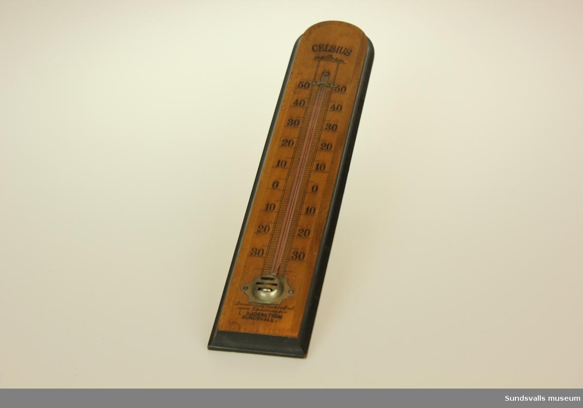 Termometer i trä, teakbetsad framsida med mörkt bruna profilerade sidor. Glasröret sprucket avsaknad av kvicksilver. Utsmyckning av växtornamentik ovan glasröret.