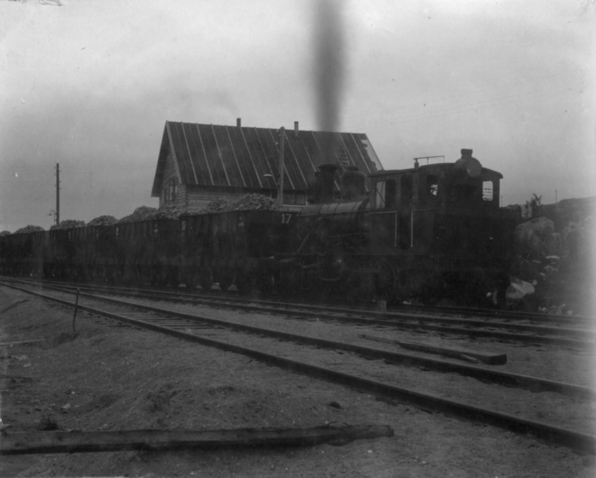 Lokomotiv og vogn. 13/7 1910. Vognene er lastet til det fulle. I bakgrunnen kan man se et hus.