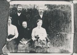Gruppeportrett av familien Halvorsæther framfor et hesjegjer