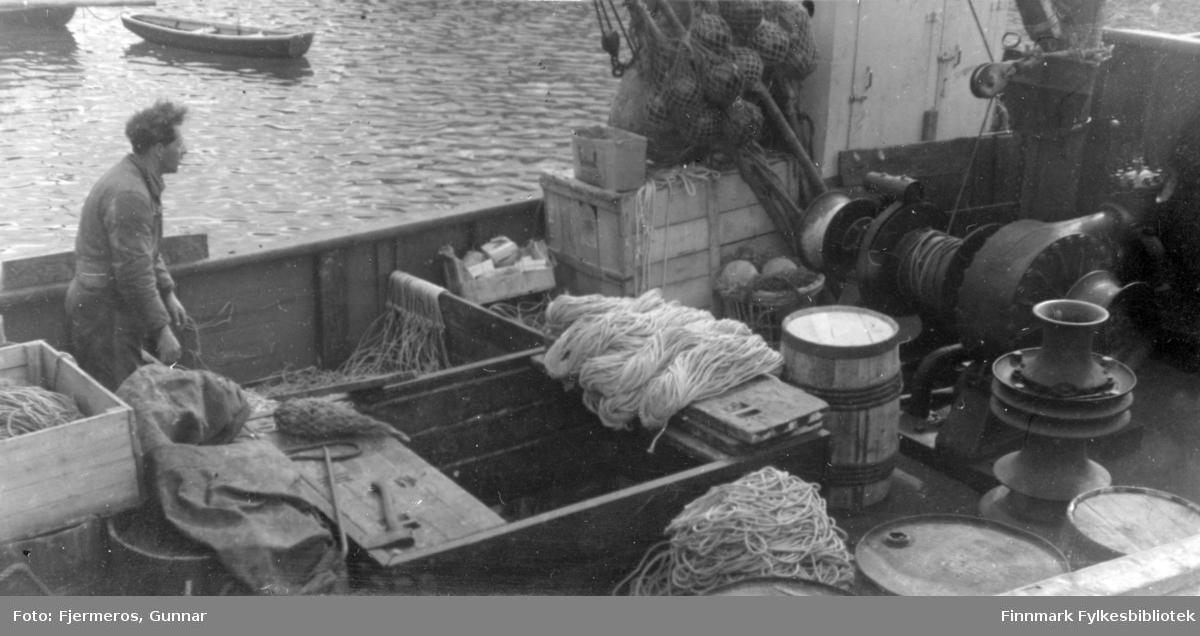 """En mann på dekket til en skøyte som akkurat har tatt ombord utstyr tili å fiske/fange Håkjerring. Person er ukjent, men båten kan være """"Varfjell"""" som muligens ligger ved kai i Kjøllefjord."""