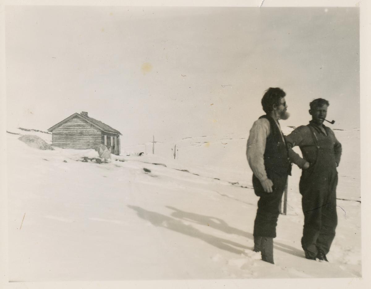 To menn nyter utsikten etter en skitur på fjellet. Ei hytte i bakgrunnen.