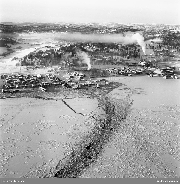 Flygfoto över Tunadal. Vinterbild med bruten isränna in mot kajen och sågverket.