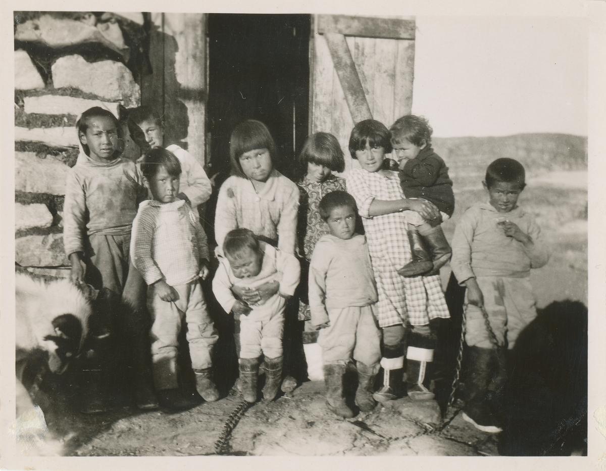 Gruppeportrett av ti grønlandske barn med en hund foran et hus.