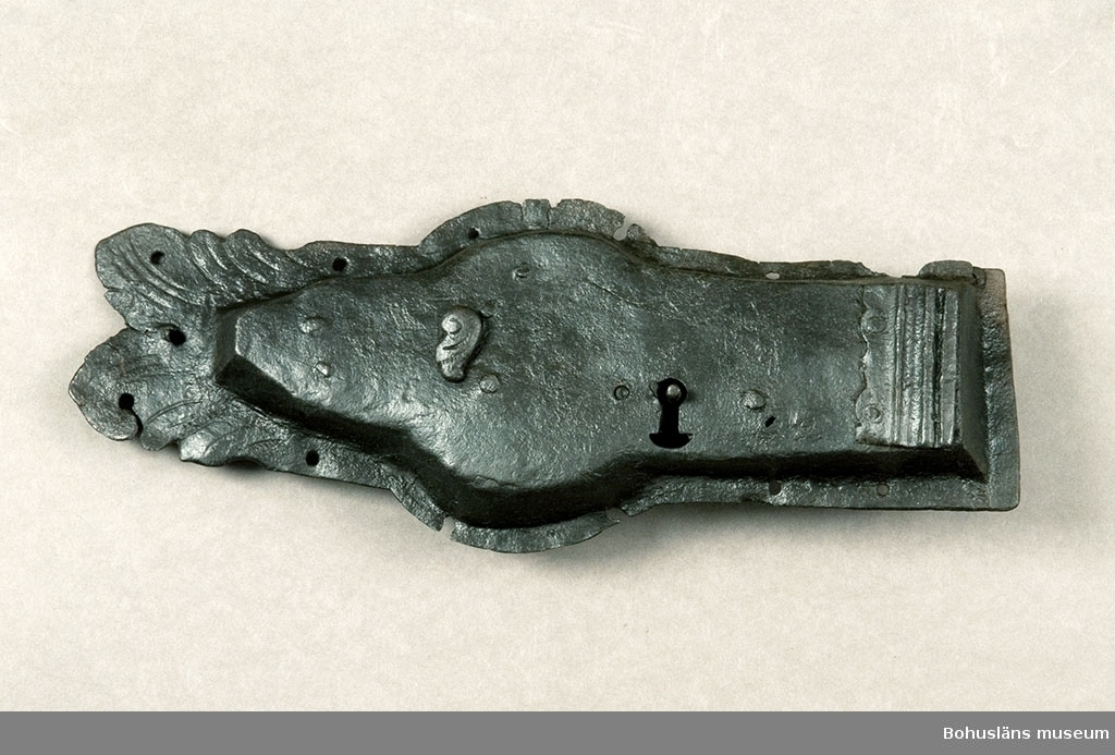 Ur handskrivna katalogen 1957-1958: Järnlås L. c:a 43 cm. Största Br. c:a 17 cm. Ålderdomlig typ. Nyckel saknas. Ngt defekt.