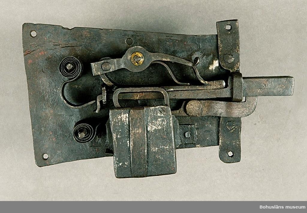 Ur handskrivna katalogen 1957-1958: Fällbomslås, m. nyckel Låset a) 30 x 16,5 x 9,5 cm; helt av järn, en bricka i mekanismen är av mässing. Helt. Nyckeln b) L. 19,5 cm m. sinnrikt ax. Hel. Lås och nyckel rostiga.