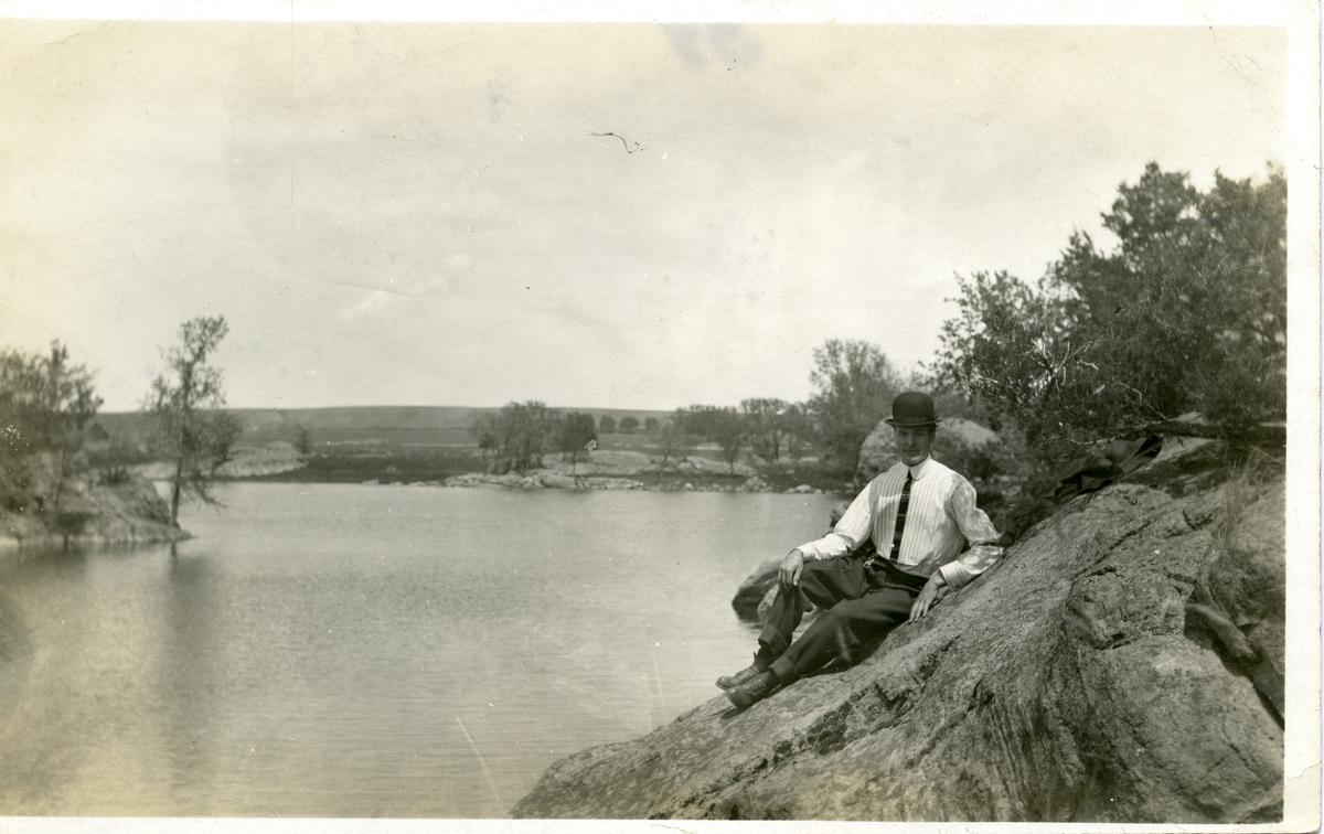 Portrett av mann liggende på stein. Mannen er iført dress og slips samt hatt. Dette er et postkort.