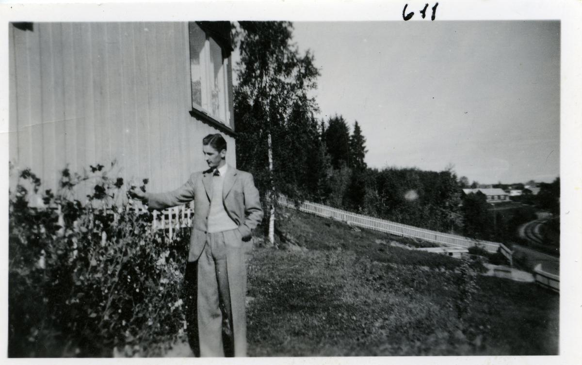 Bildet viser en ung mann som står ved en rosebusk utenfor et hus. Toralv Buskern fra Skreia