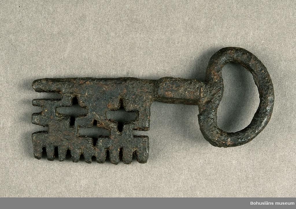 Ur handskrivna katalogen 1957-1958: Nyckel L. 8,5 cm. Br. 3 cm. Järnnyckel till konstlås. Genombruten m. korsformat mönster bl.a.  Mkt. förrostad.