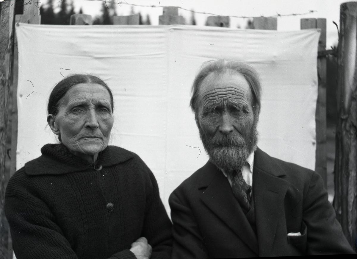 Kvinne og mann (mann og kone?)avbildet i halvfigur. De sitter foran et laken som er stiftet fast til et gjerde med piggtråd på toppen.