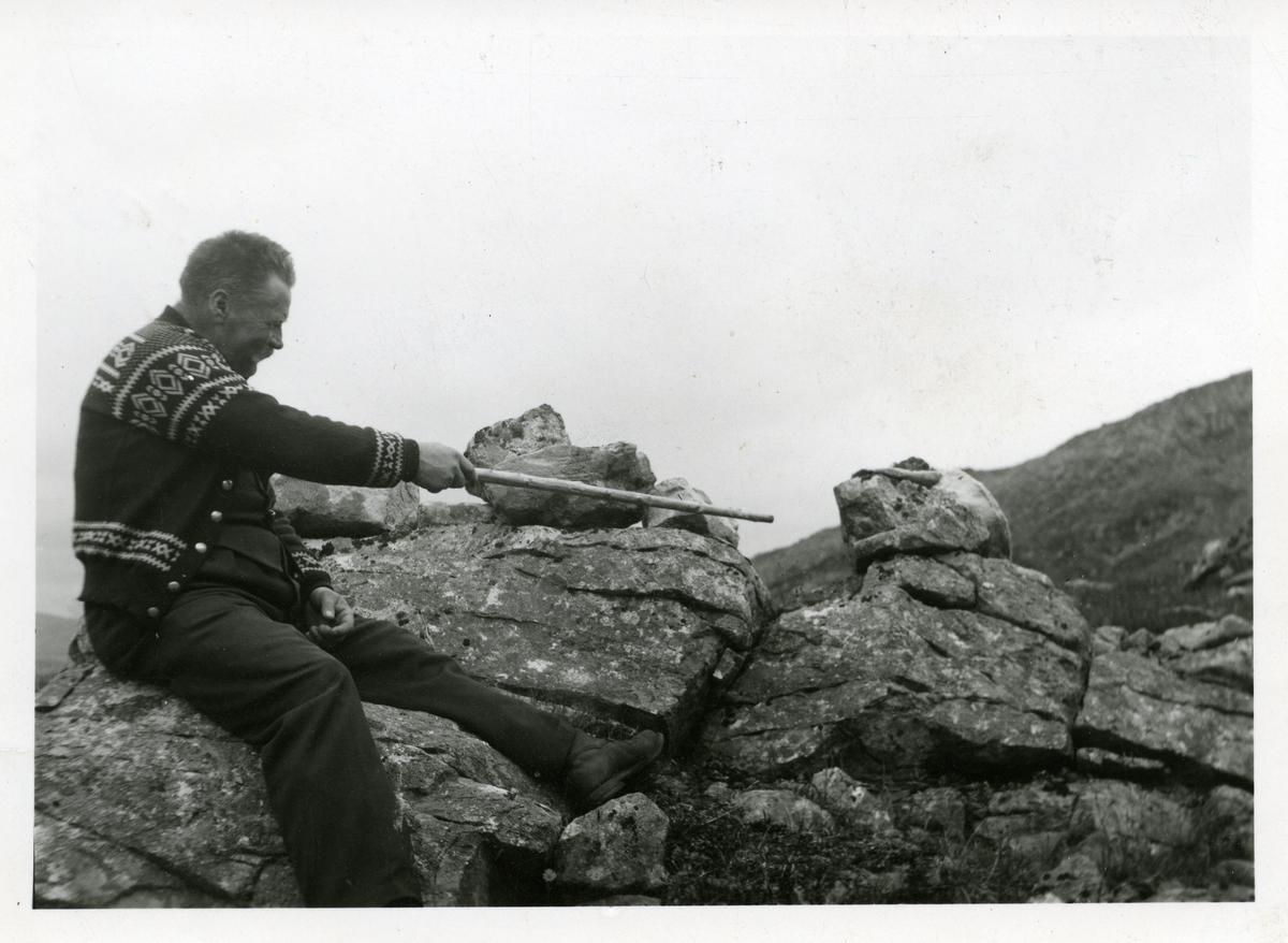 En mann i lusekofte sitter på noen steiner og peker med en pinne på restene etter en skyteglugge.