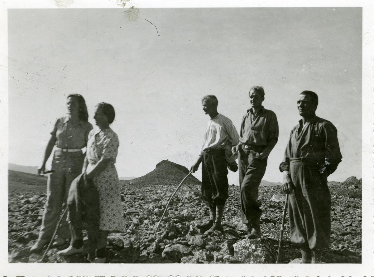 To kvinner og tre menn avbildet foran en fjellknaus i Valdres.