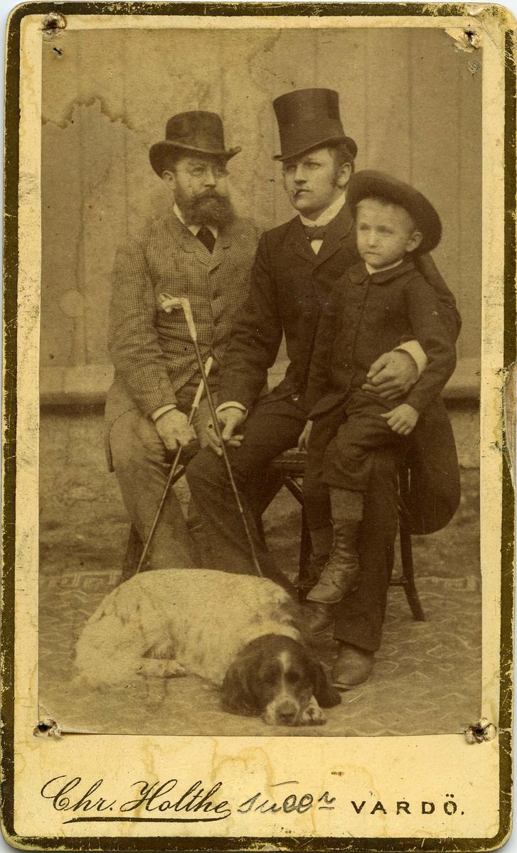 To ukjente menn og en liten gutt. Gutten sitter på fanget til den yngste mannen. Den eldre mannen med skjegg kan være Bersvend Thoresen.