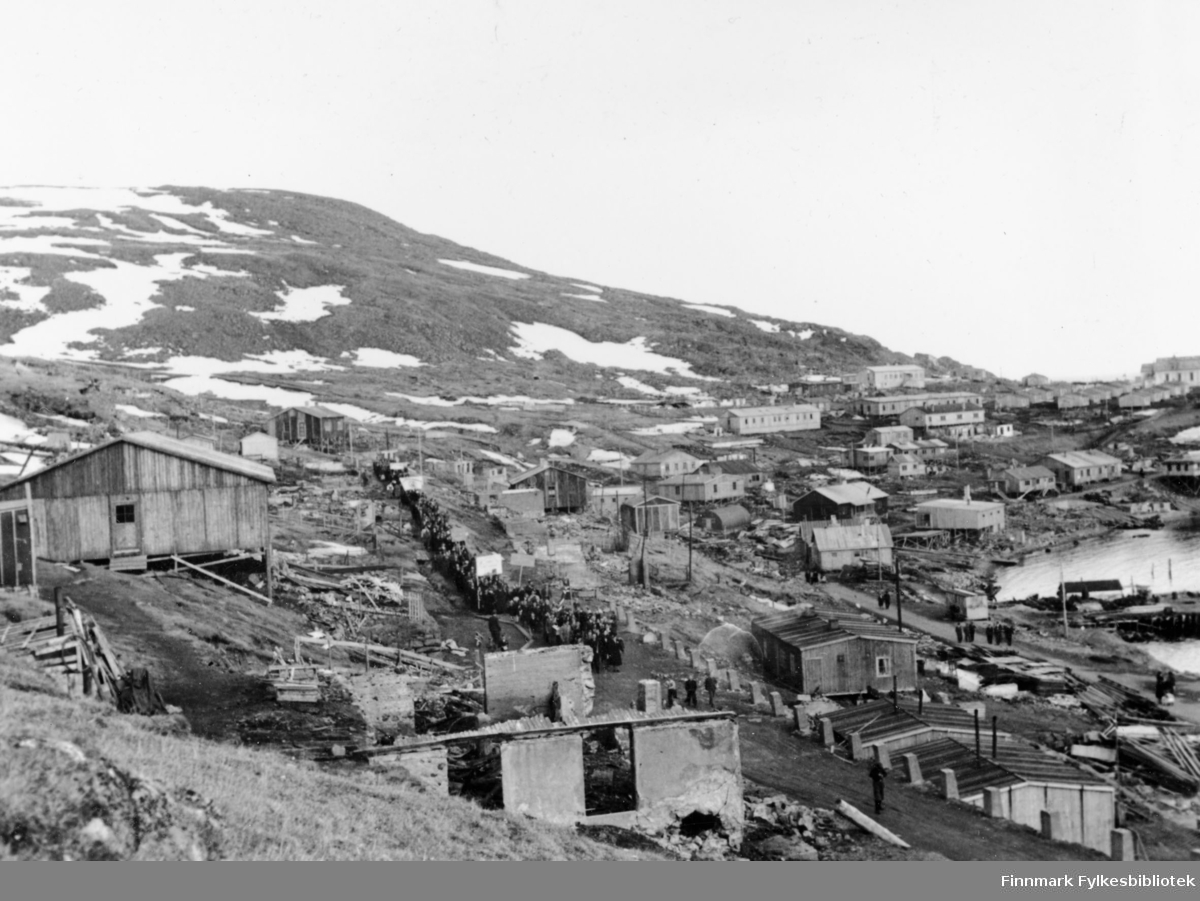 Honningsvåg, 1947. En gruppe mennesker marsjerer i et tog i gaten.