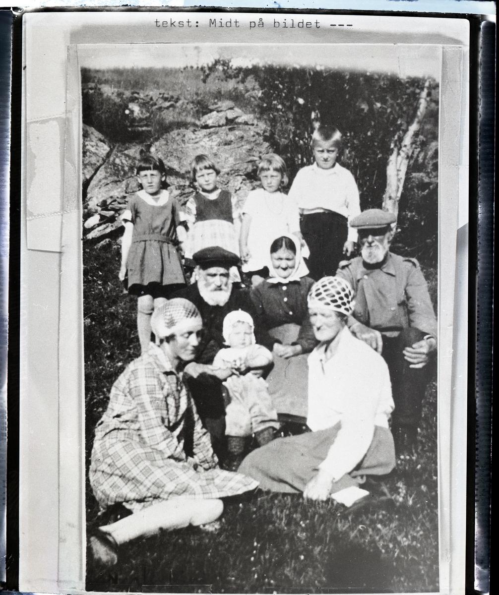 Eldre mann og kvinne (søsken) sitter i graset foran en steinmur med et spebarn på fanget. To kvinner sitter foran, begge har heklete luer på seg.  Ved siden av ekteparet sitter en mann med hvitt skjegg og flere barn står bak dem. Dette er husmannsplassen Tyrilie under Nerre Ton 32/1