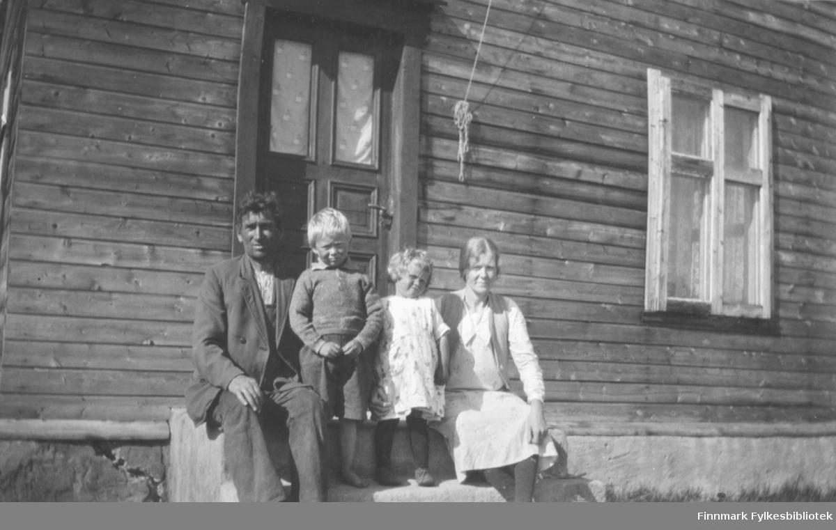 """""""Familien Hanna og Andreas Nikoma. Fra venstre: Andreas Nikoma, Arnfinn Nikoma, Asbjørg (Søssa) Nikoma og Hanna Nikoma. Hanna var fra Trøndelag. Familien sitter foran Nikoma-huset like ved veien i Vestre Jakobselv."""""""