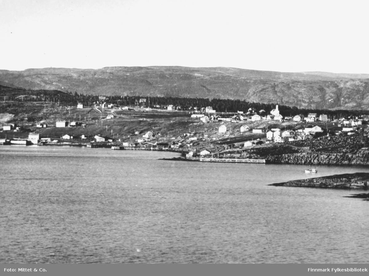 Et fotografi av Bossekop, Alta. På bildet kan man se flere hus og en kirke. På havet kan man se en fiskebåt.