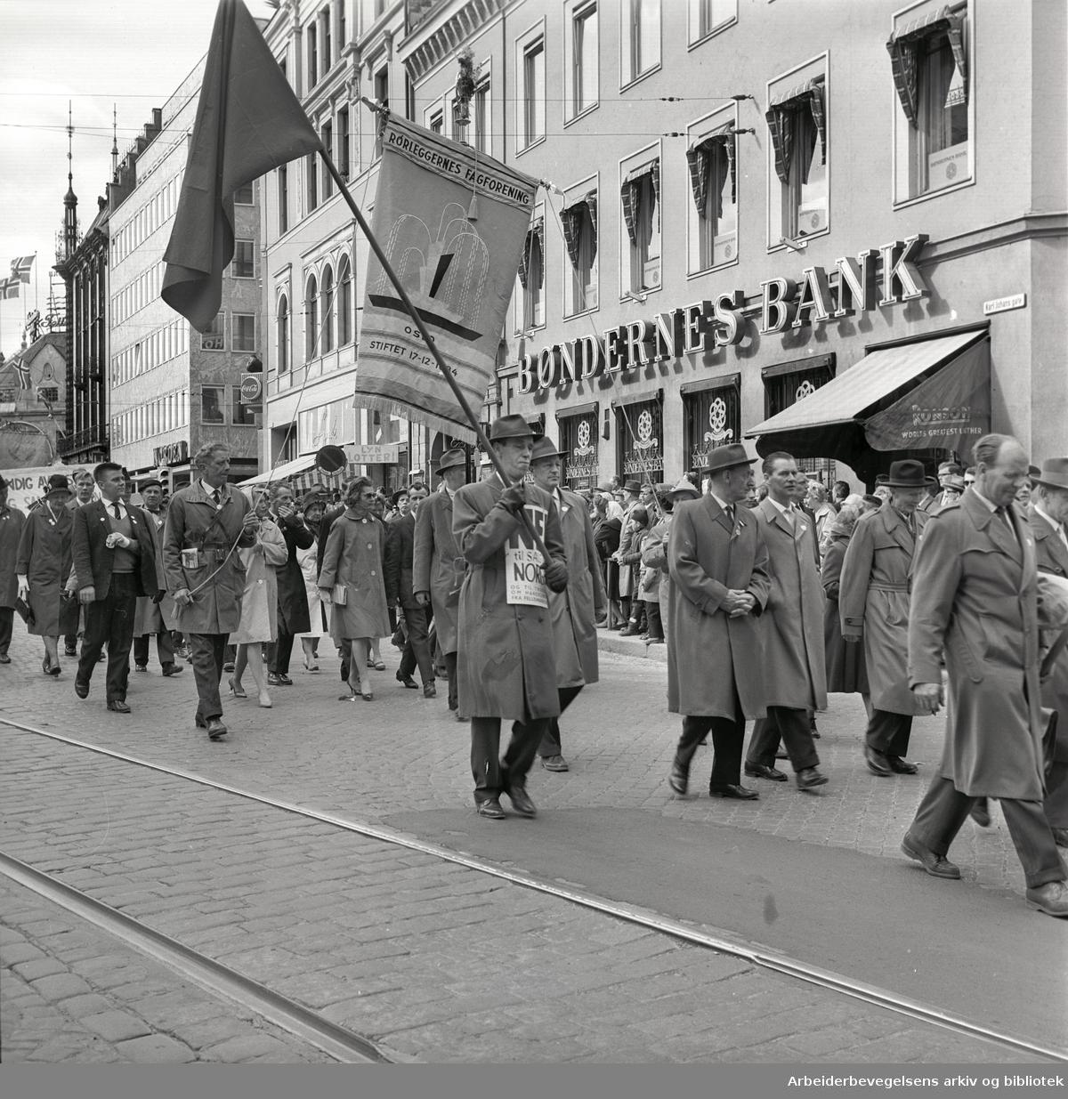 """1. mai 1962 i Oslo.Demonstrasjonstog arrangert av """"Faglig aksjon mot Fellesmarkedet"""" med støtte fra Sosialistisk Folkeparti (SF) og Norges kommunistiske parti (NKP)..Fane: Rørleggernes fagforening."""