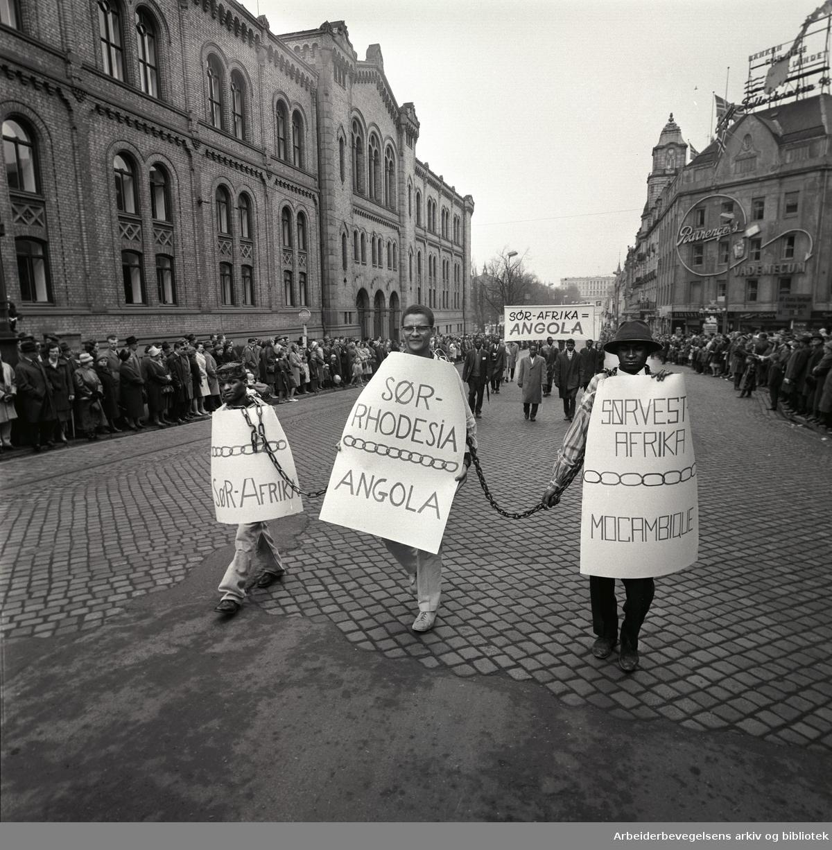 1. mai 1963 i Oslo.Demonstrasjonstoget i Karl Johans gate..Afrikanske studenter, i midten Hans Beukers. .Parole: Sør-Afrika.Parole: Sør-Rhodesia Angola.Parole: Sørvest-Afrika Mocambique.I midten: Hans Beukes.
