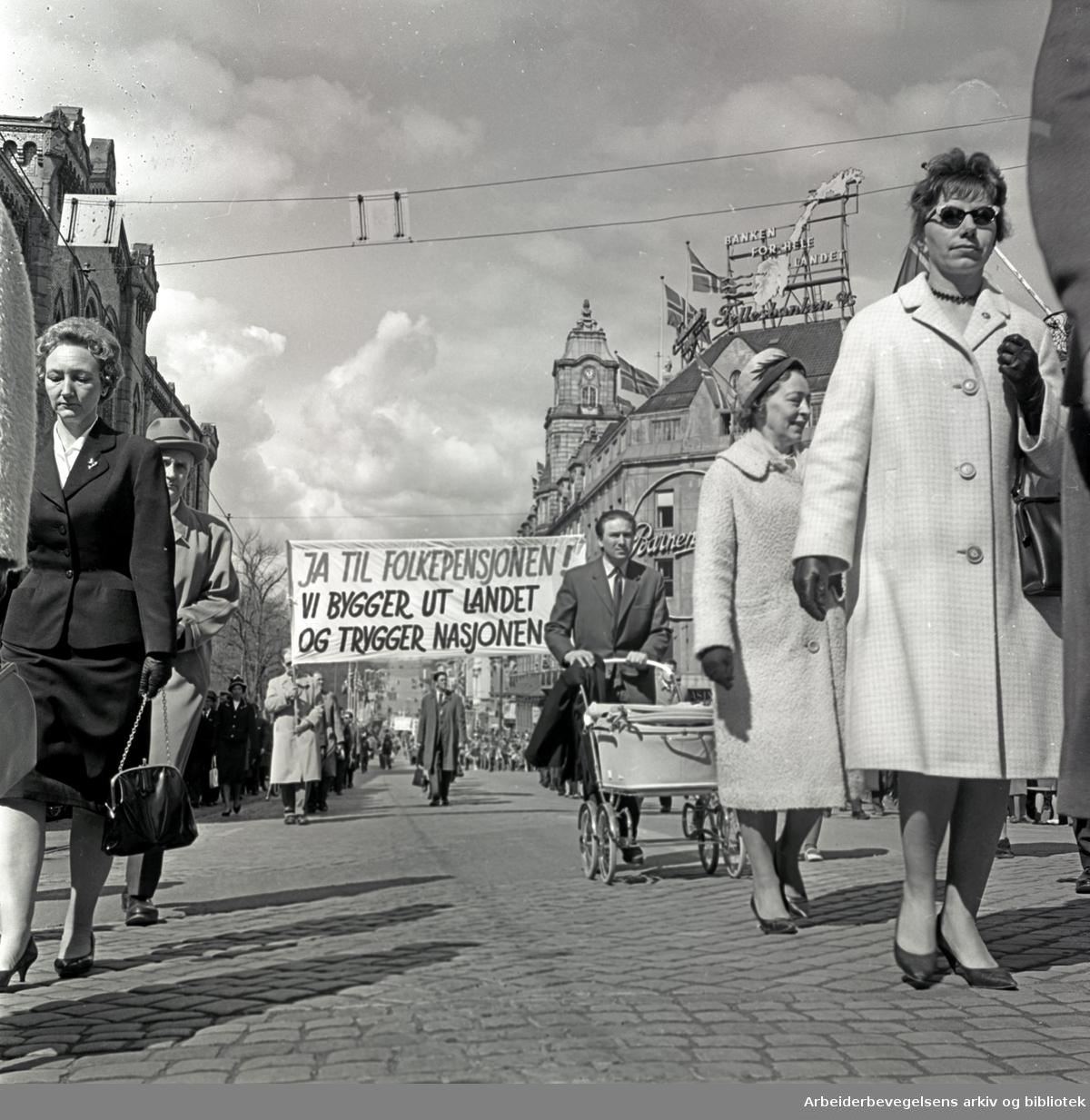 1. mai 1964 i Oslo.Demonstrasjonstoget i Karl Johans gate.Parole: Ja til folkepensjonen!.Vi bygger ut landet og trygger nasjonen