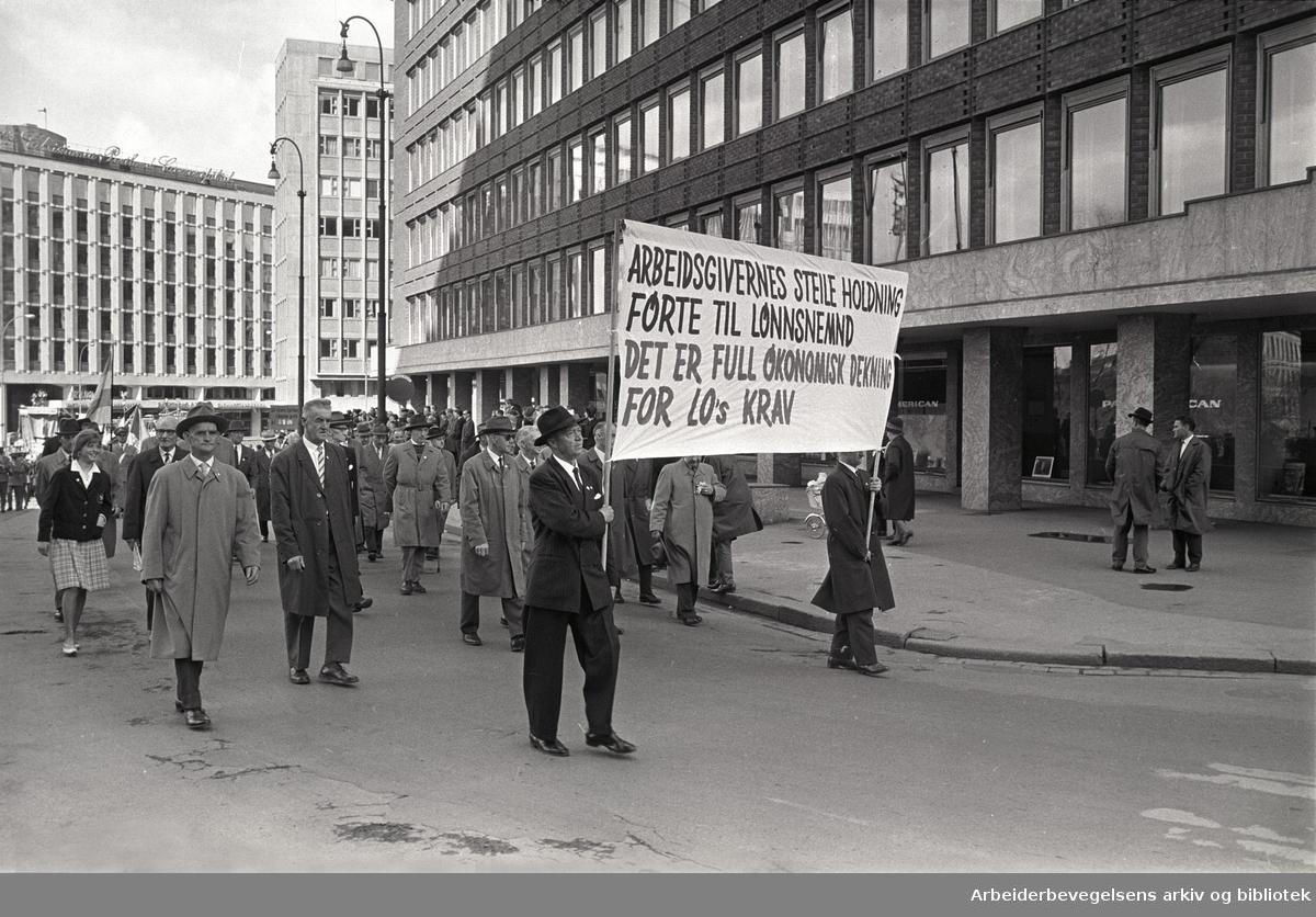 1. mai 1964 i Oslo.Demonstrasjonstoget ved Rådhusplassen.Parole: Arbeidsgivernes steile holdning.førte til lønnsnemd .Det er full økonomisk dekning for LOs krav.