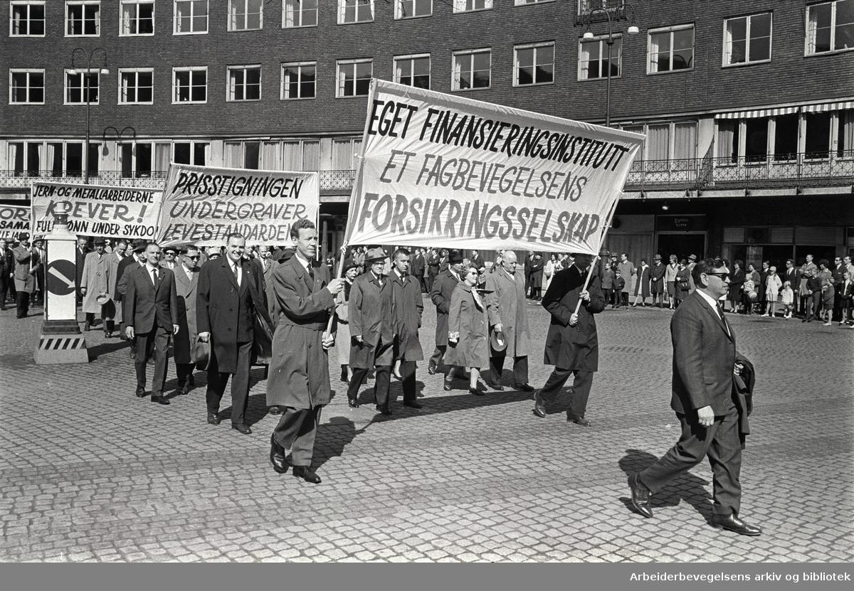 1. mai 1964 i Oslo.Demonstrasjonstoget ved Rådhusplassen.Parole: Eget finansieringsinstitutt.et fagbevegelsens forsikringsselskap.Parole: Prisstigningen undergraver levestandarden.Parole: Jern- og Metallarbeiderne krever! Full lønn under sykdom