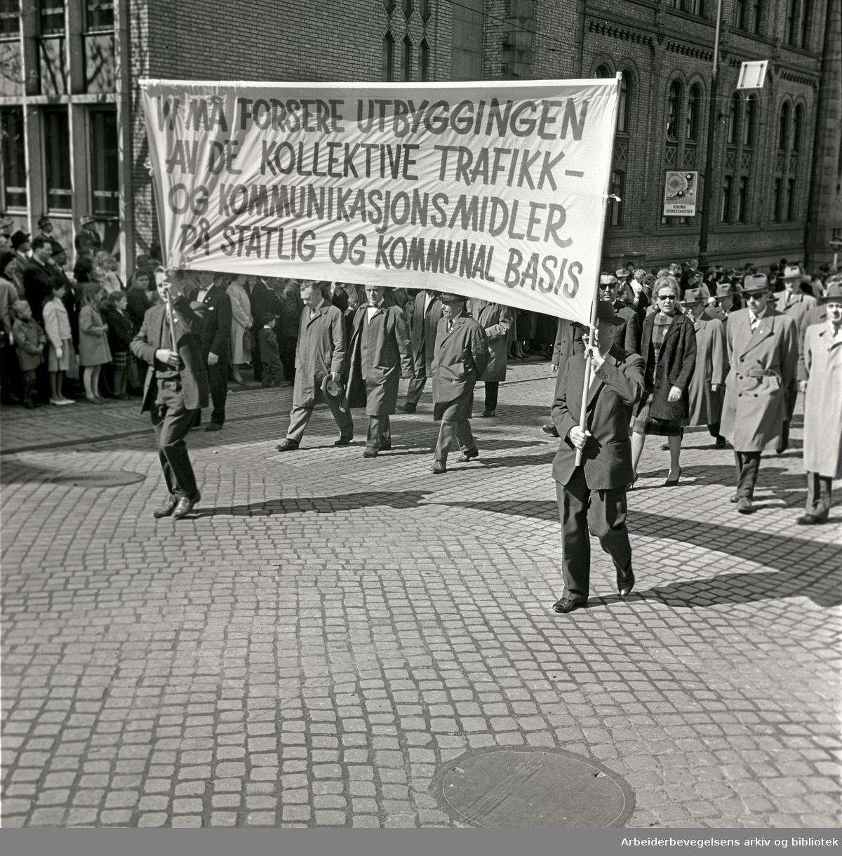 1. mai 1964 i Oslo.Demonstrasjonstoget i Karl Johans gate.Parole: Vi må forsere utbyggingen av de kollektive trafikk- og kommunikasjonsmidler på statlig og kommunal basis