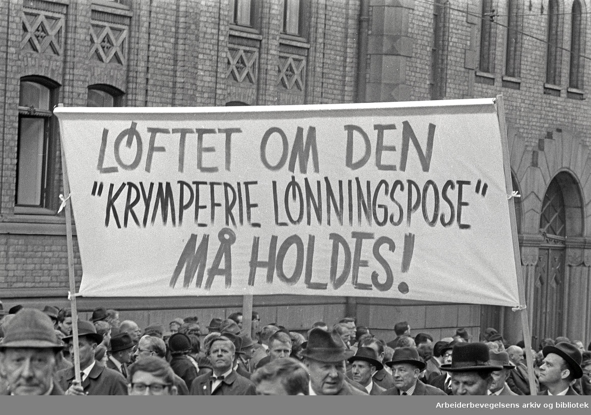 "1. mai 1966 i Oslo.Demonstrasjonstoget i Karl Johansgate.Parole: Løftet om den ""krympefrie lønningspose"" må holdes!"
